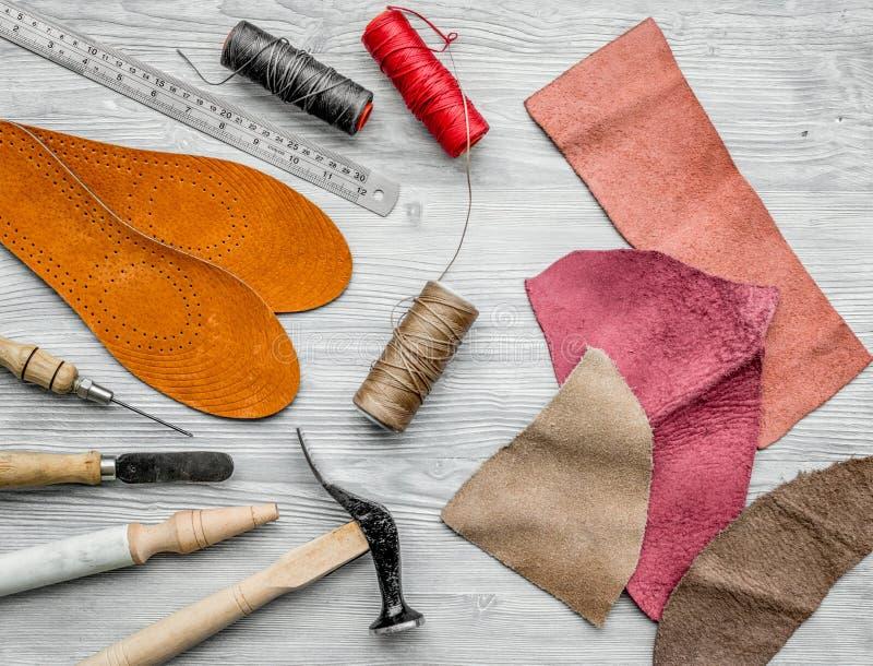 Werkende plaats van schoenmaker Huid en hulpmiddelen op grijze houten bureau hoogste mening als achtergrond royalty-vrije stock afbeeldingen