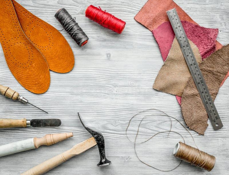 Werkende plaats van schoenmaker Huid en hulpmiddelen op grijze houten bureau hoogste mening als achtergrond copyspace royalty-vrije stock afbeeldingen