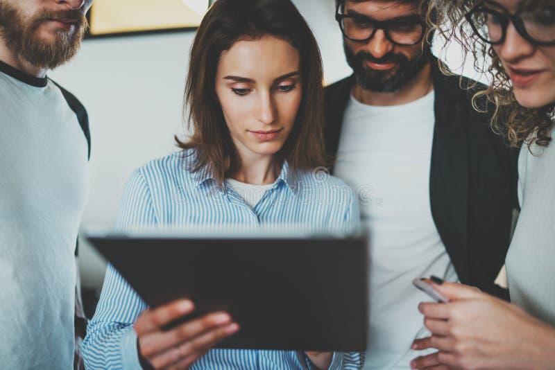 Werkende procesfoto Groep jonge medewerkers die elektronische gadgets gebruiken samen bij moderne bureauzolder stock afbeeldingen