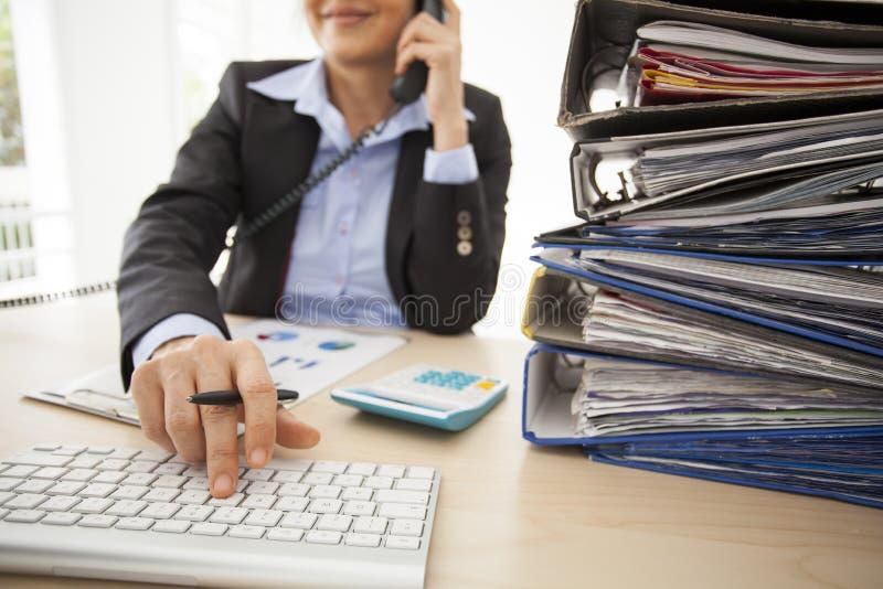 Werkende vrouw in het bureau stock foto