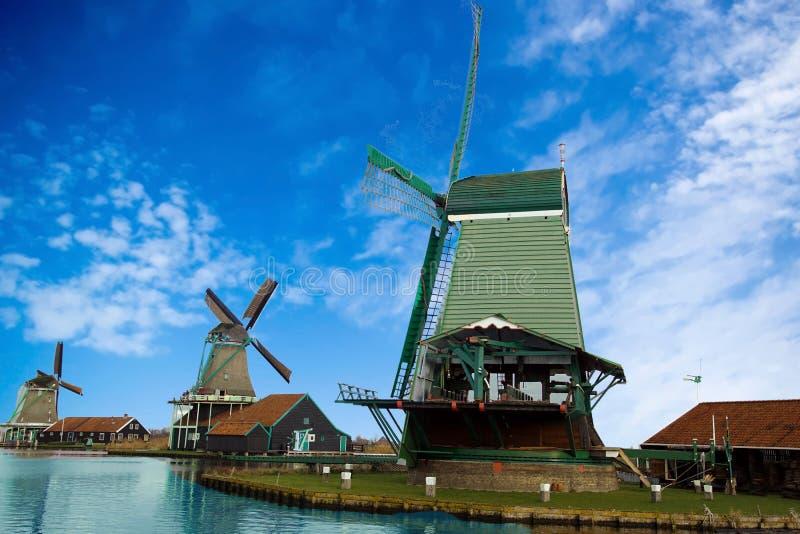 Werkende windmolens op kanaal stock afbeelding
