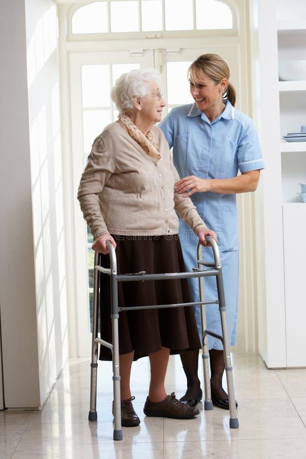 Werker uit de hulpverlening die Bejaarde Hogere Vrouw helpt die het Lopen F gebruikt stock afbeelding