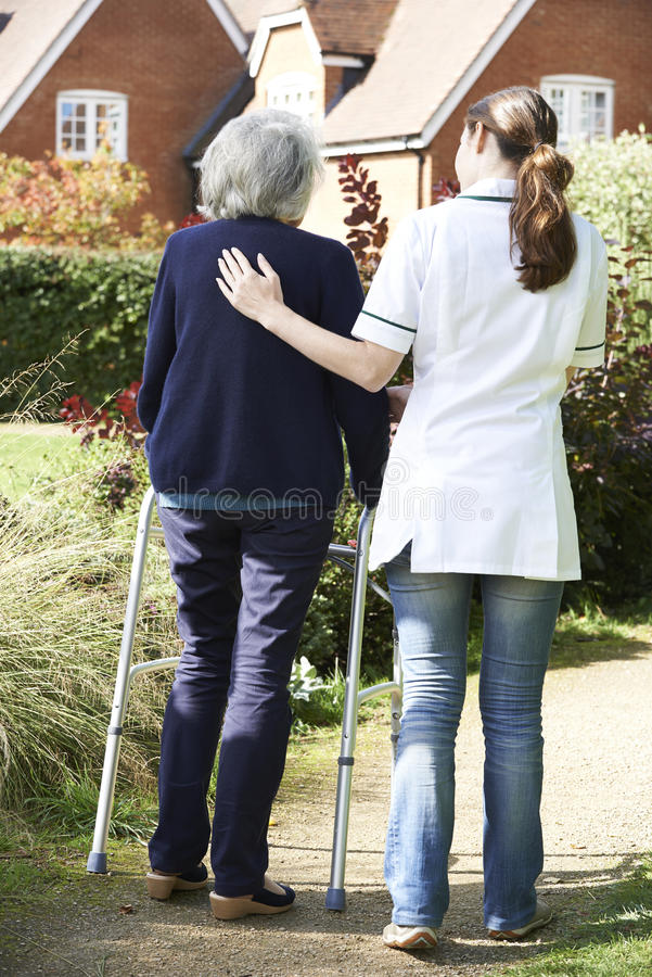 Werker uit de hulpverlening die Hogere Vrouw helpen om in Tuin te lopen die het Lopen Kader gebruiken royalty-vrije stock fotografie