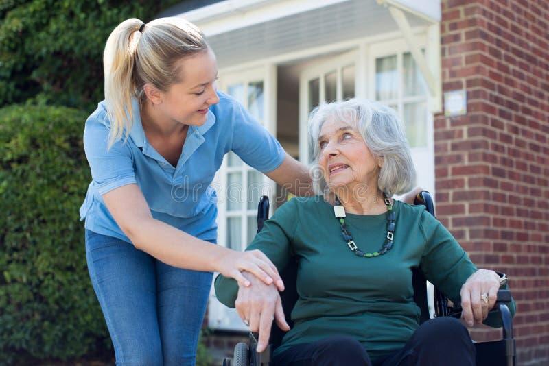 Werker uit de hulpverlening die Hogere Vrouw in Rolstoel buiten Huis duwen stock afbeelding