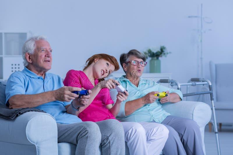 Werker uit de hulpverlening het spelen videospelletjes met bejaard paar stock afbeeldingen