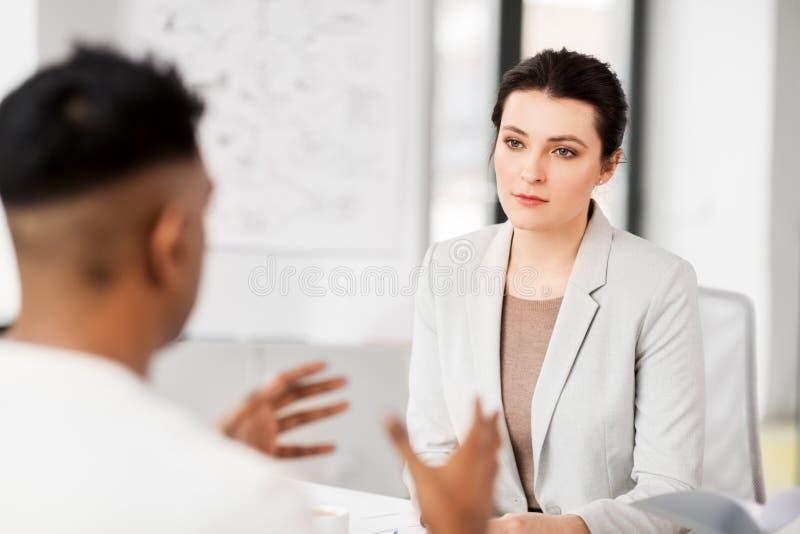 Werkgever die gesprek met werknemer hebben op kantoor stock afbeeldingen