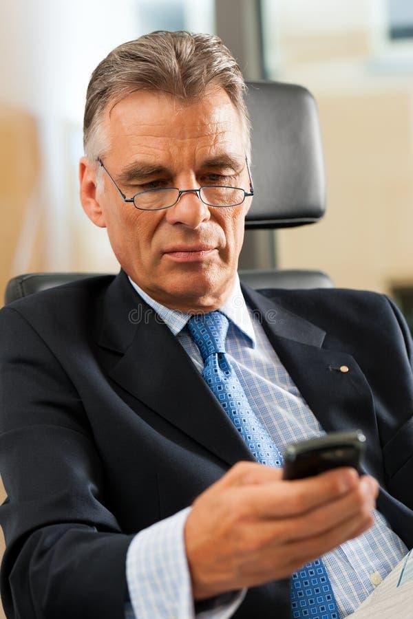 Werkgever die in zijn bureau e-mail controleert stock afbeelding