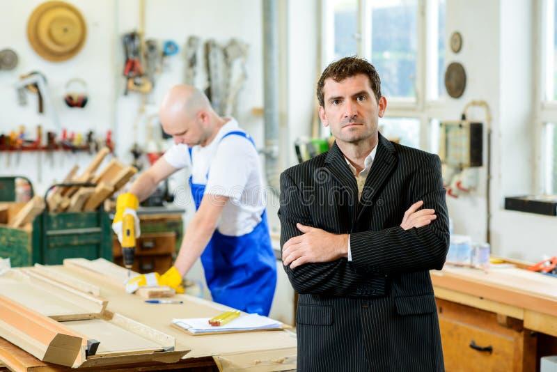Werkgever en arbeider in een timmermans` s workshop stock afbeelding