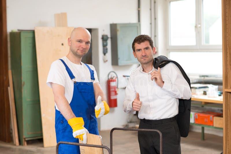 Werkgever en arbeider met duim omhoog in een timmermans` s workshop stock foto