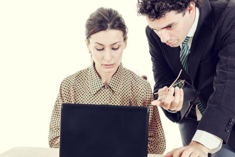 Werkgever en secretaresse die aan laptop samenwerken stock foto