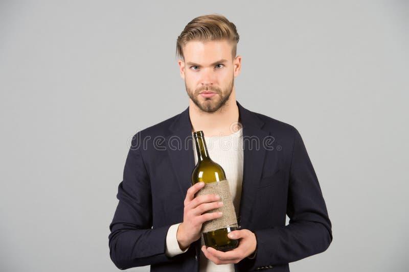 Werkgever met fles wijn in handen De gebaarde alcoholische drank van de mensengreep Sommelier of degustator met wijn Alcoholversl royalty-vrije stock afbeelding