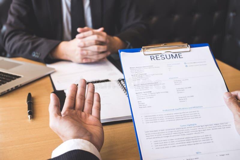 Werkgever of recruiter de holding die een samenvatting lezen tijdens ongeveer zijn profiel van kandidaat, werkgever in kostuum le stock fotografie