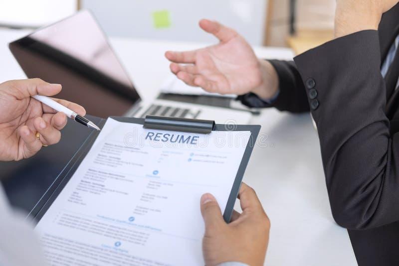 Werkgever of recruiter de holding die een samenvatting tijdens ongeveer onderhoud zijn profiel van kandidaat, werkgever in kostuu stock afbeelding
