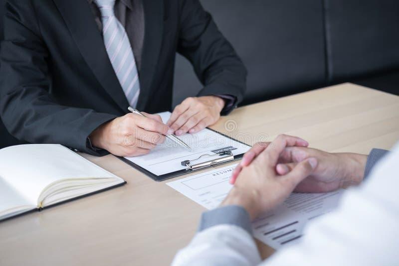 Werkgever of recruiter de holding die een samenvatting tijdens ongeveer onderhoud zijn profiel van kandidaat, werkgever in kostuu royalty-vrije stock afbeeldingen
