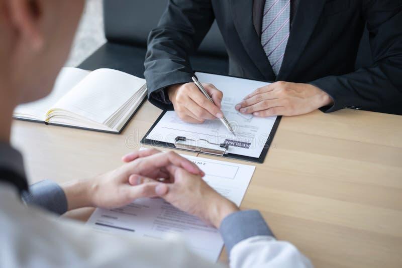 Werkgever of recruiter de holding die een samenvatting tijdens ongeveer onderhoud zijn profiel van kandidaat, werkgever in kostuu royalty-vrije stock fotografie