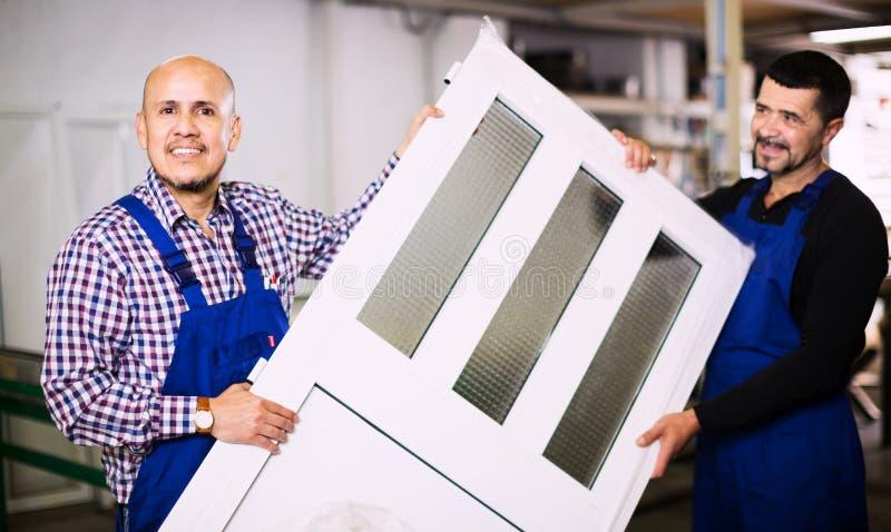 Werklieden die pvc-productieoutput inspecteren stock afbeeldingen