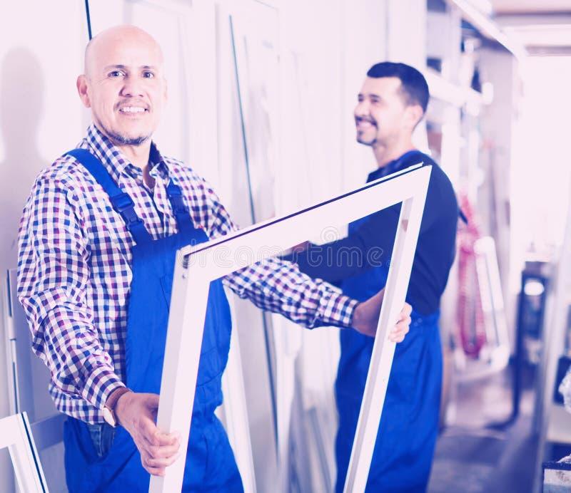 Werklieden die pvc-productieoutput inspecteren stock fotografie
