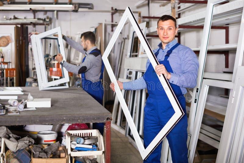 Werklieden die pvc-productieoutput in workshop inspecteren stock fotografie