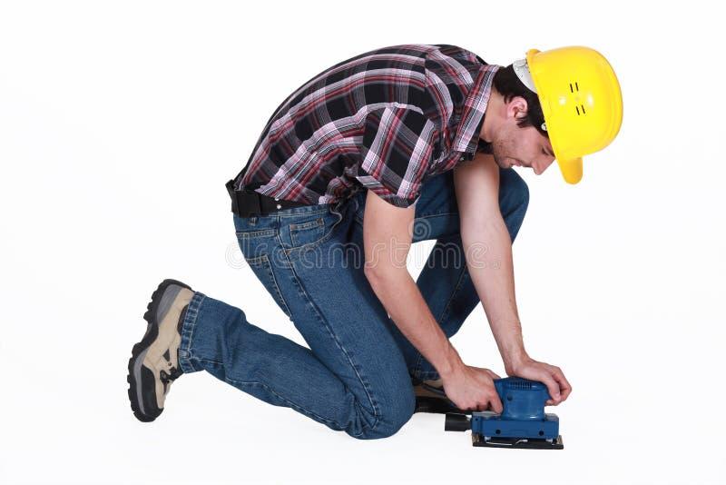 Werkman die een elektrische schuurmachine met behulp van royalty-vrije stock afbeeldingen