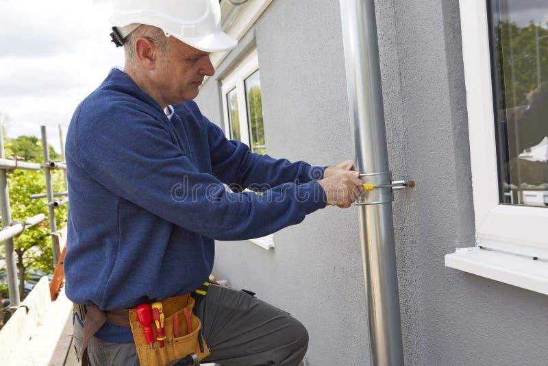 Werkman die Guttering op Buitenkant van Huis vervangen stock foto