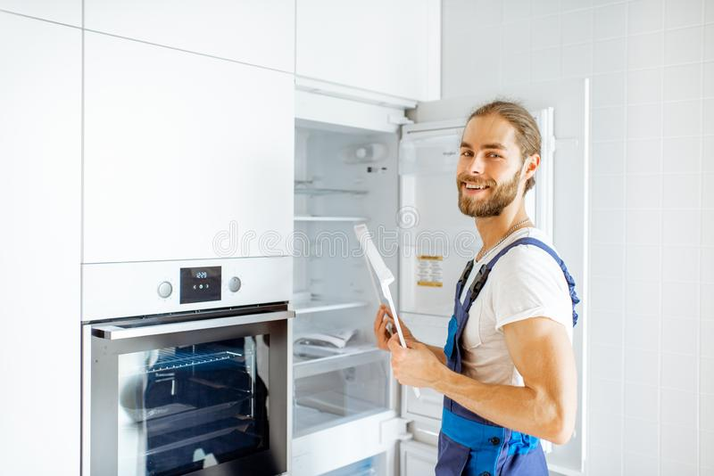 Werkman die koelkast thuis installeren op de keuken royalty-vrije stock afbeeldingen