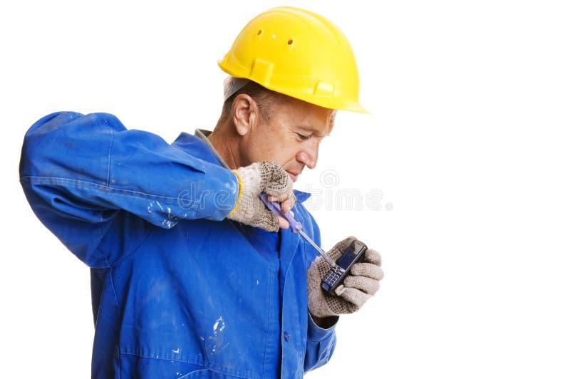 Werkman die mobiele telefoon bevestigt stock foto