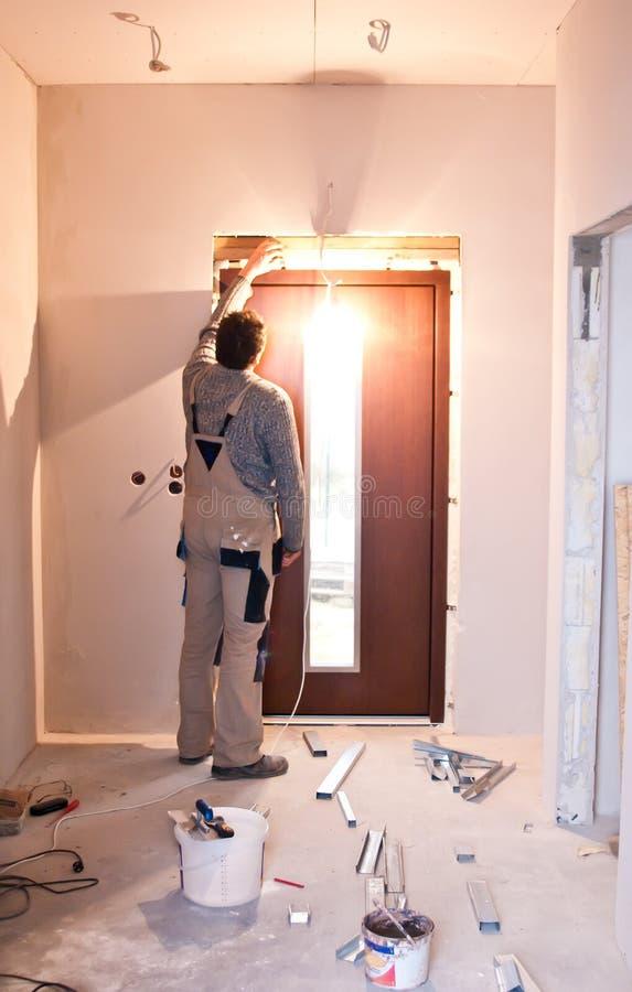 Werkman die nieuwe deur installeren royalty-vrije stock afbeeldingen
