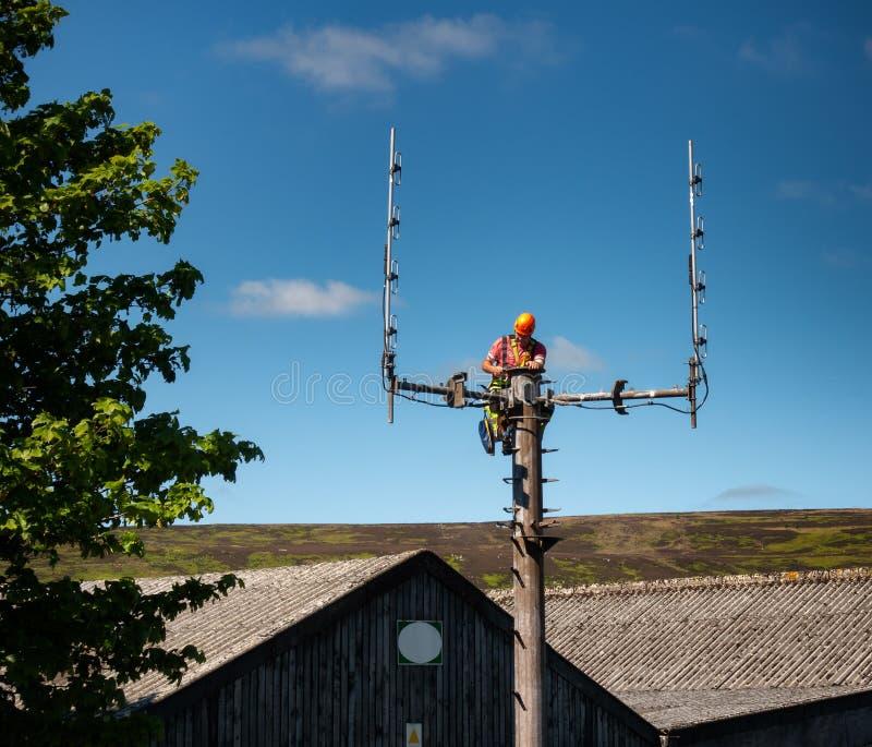 Werkman die wijzigingen maken aan een Airwaves-Hulpdiensten radiomast stock afbeelding