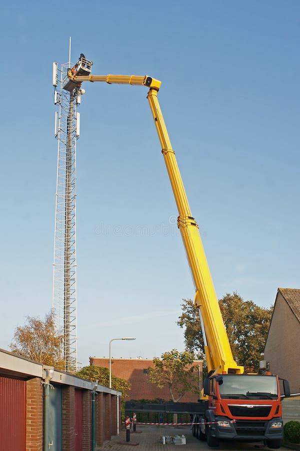 Werkman in een hydraulisch hijstoestel die installatie van een hoge telephonemast herstellen royalty-vrije stock foto