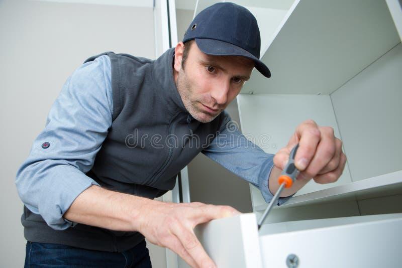Werkman het bevestigen keukenlade met schroevedraaier royalty-vrije stock foto's