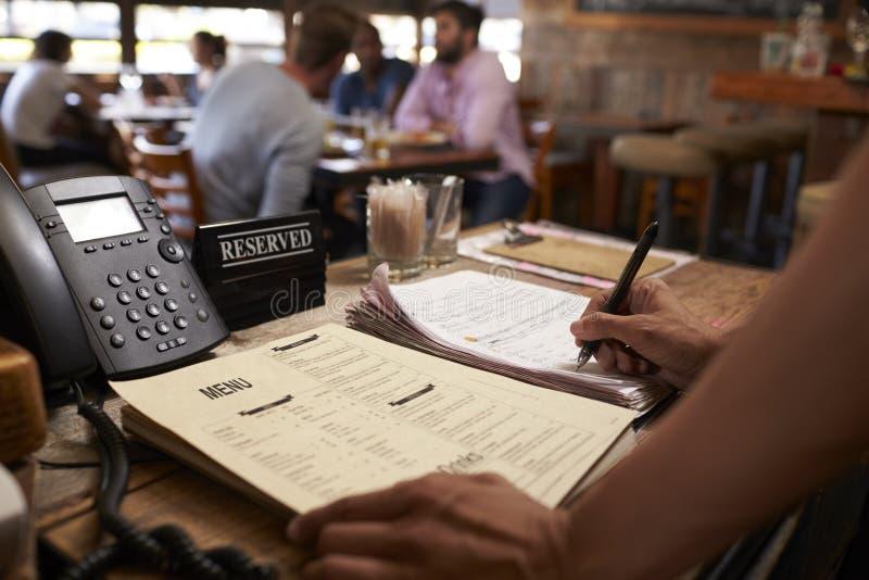 Werknemer bij een restaurant die een lijstreserve neerschrijven stock foto