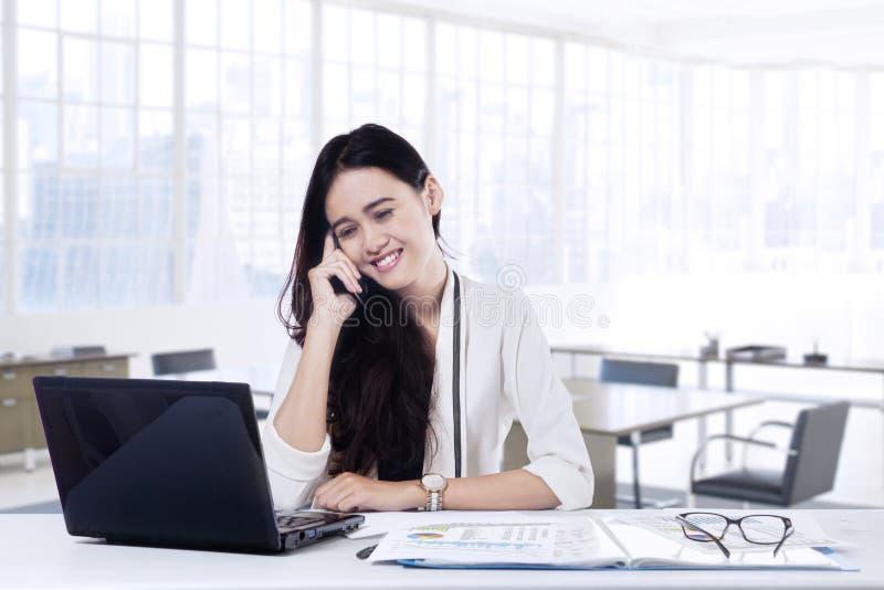 Werknemer die op de mobiele telefoon in bureau spreken royalty-vrije stock foto