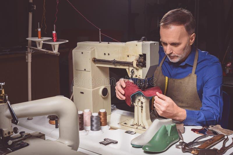 Werknemer die schoenen op de naaimachine maken royalty-vrije stock fotografie