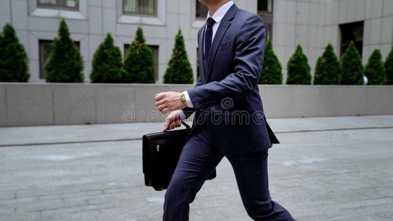 Werknemer die zich aan baan haasten, die aan de bureaubouw lopen, tijdbeheer, spitsuur royalty-vrije stock afbeeldingen