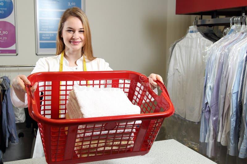 Werknemer van een chemisch reinigen met een wasmand stock fotografie