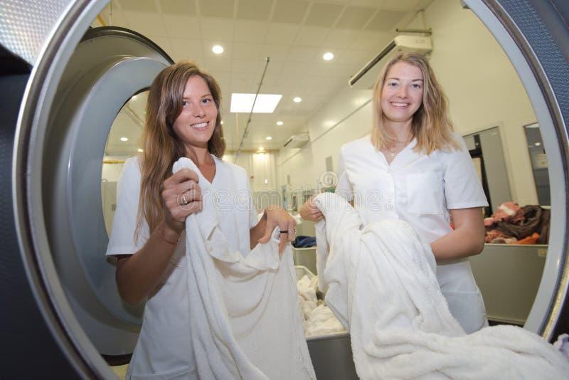 Werknemers de professionele wasmachine van chemisch reinigenladingen stock foto's