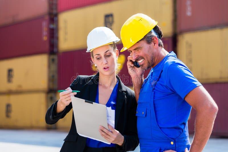 Werknemers in de verschepende containers van het logistiekbedrijf royalty-vrije stock afbeeldingen