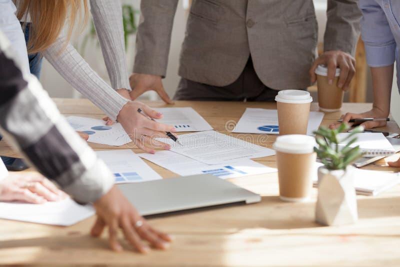 Werknemersuitwisseling van ideeën met documenten op lijst tijdens vergadering royalty-vrije stock foto's