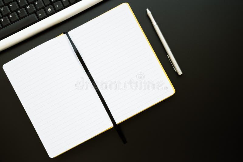Werkplaats met notebooks, pen en toetsenbord op de zwarte desk Mock-up Bovenaanzicht Vlek Kopieerruimte stock afbeelding