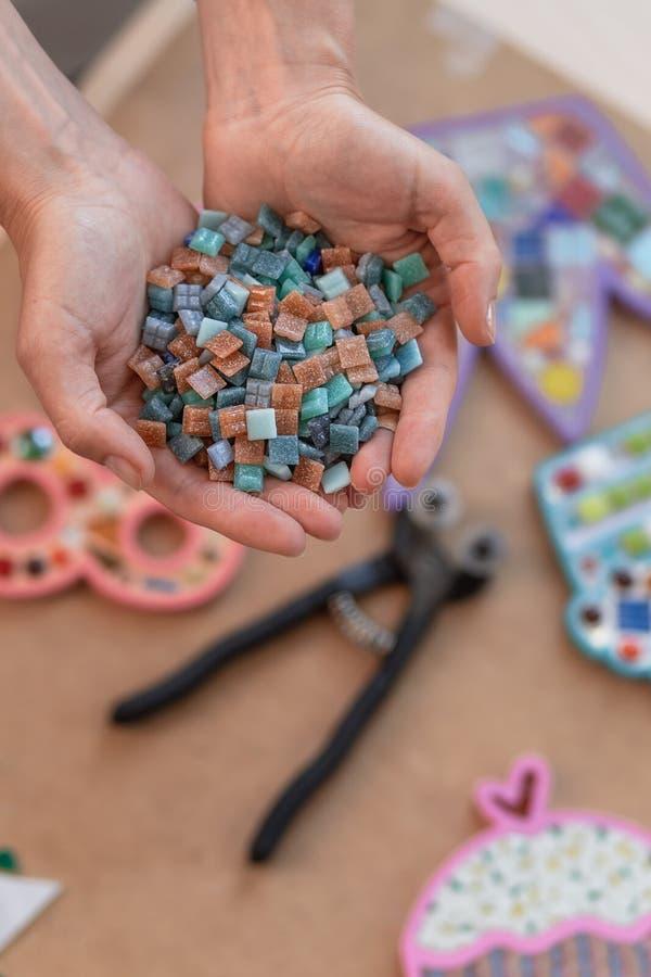 Werkplaats van de mozaïekmeester: vrouwen` s handen die mozaïekdetails tijdens het maken van een mozaïek houden stock afbeeldingen