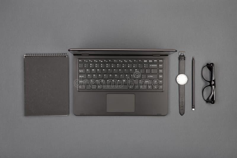 werkplaats van zakenman - laptop, glazen en blocnote stock afbeelding