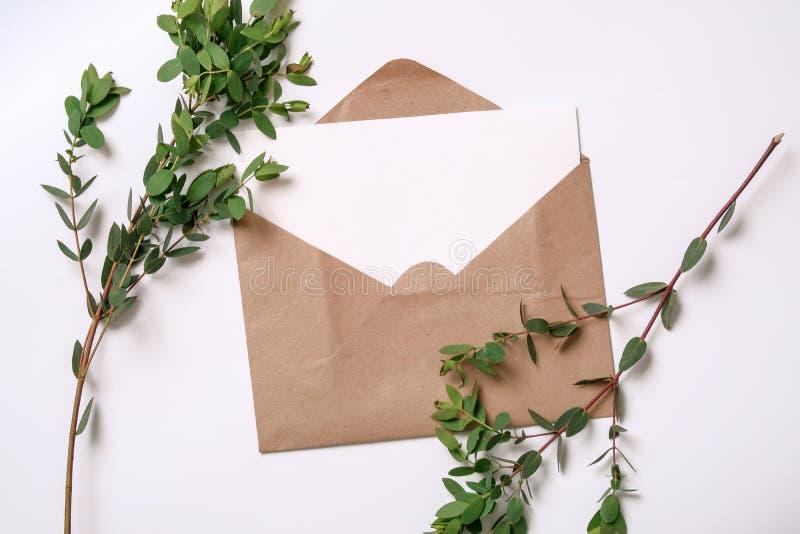 werkruimte De kaarten van de huwelijksuitnodiging, kraftpapier-enveloppen, groene bladeren royalty-vrije stock foto