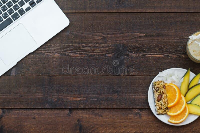 Werkruimte met laptop en met een gezond ontbijt: mango, orang-oetan royalty-vrije stock afbeelding