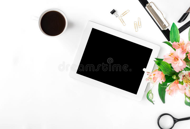 Werkruimte met tablet, bureautoebehoren, koffie en boeket van stock afbeelding