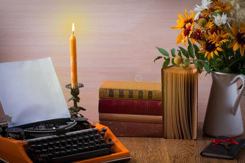 Werkruimte met uitstekende oranje schrijfmachine Boeket van de zomerbloemen, kaarsen, oude boeken en uitstekende sleutel stock afbeeldingen