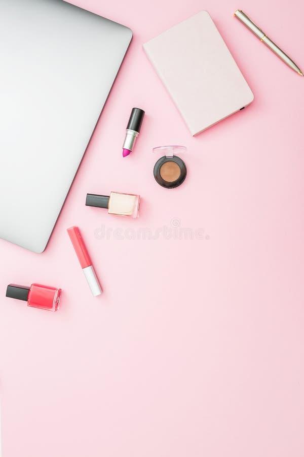 Werkruimte van het huis de vrouwelijke bureau met laptop, notitieboekje en schoonheidsmiddelen op roze achtergrond Hoogste mening royalty-vrije stock afbeelding