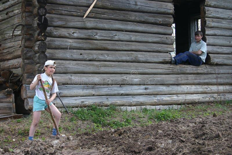 Werkt het plattelands Russische meisje de grond gebruikend een spade stock fotografie
