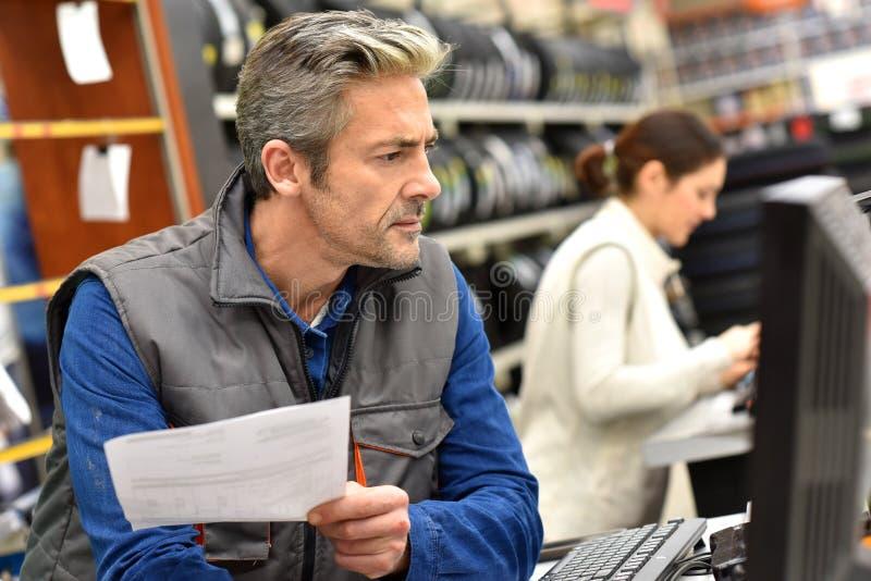 Werktuigkundige in autowinkel die aan computer werken stock afbeelding