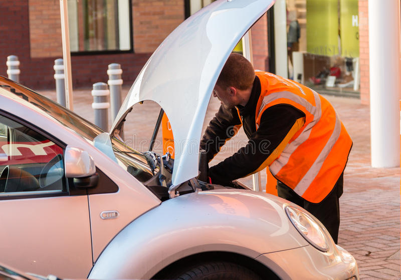 Werktuigkundige die aan een auto met de omhoog bonnet (kap) werken stock fotografie