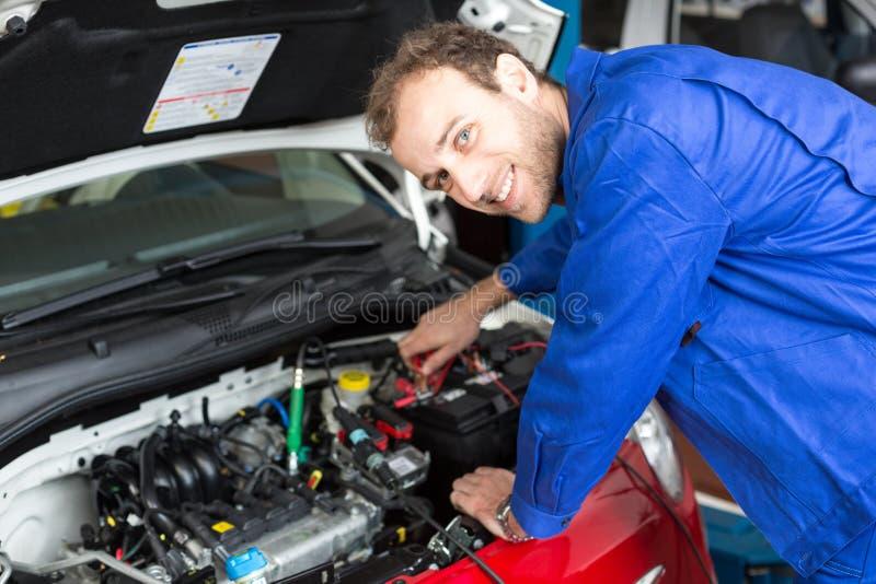 Werktuigkundige die een auto in een workshop of een garage herstellen royalty-vrije stock foto's